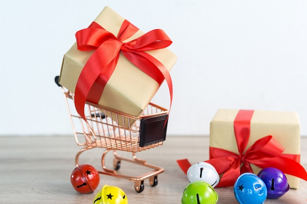 Shopping cart with christmas gifts box red ribbon and colorful bell on wood