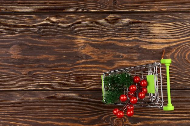 木製の背景にクリスマスショッピングとショッピングカート。ミニマルなスキャンディスタイル。上面図、フラットスタイル。