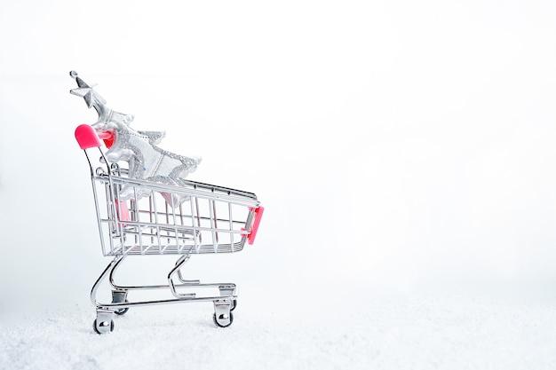 흰색 배경에 고립 된 크리스마스 트리 쇼핑 카트. 크리스마스와 새해를 위한 준비의 개념입니다.