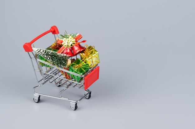 Shopping cart with christmas tree and miniature gift boxes on gray background