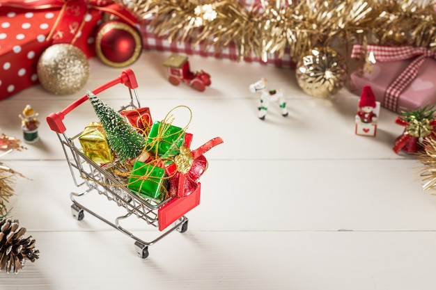 Shopping cart with christmas tree and miniature gift boxes on white wood