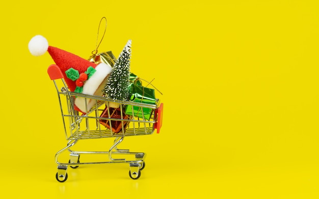 Shopping cart with christmas tree and miniature gift boxes on yellow background