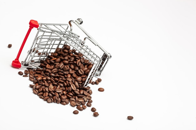 白い背景の上のコーヒー豆とショッピングカート。豆のカートがひっくり返り、テーブルにコーヒーをこぼした。コーヒー業界の概念を分離します。