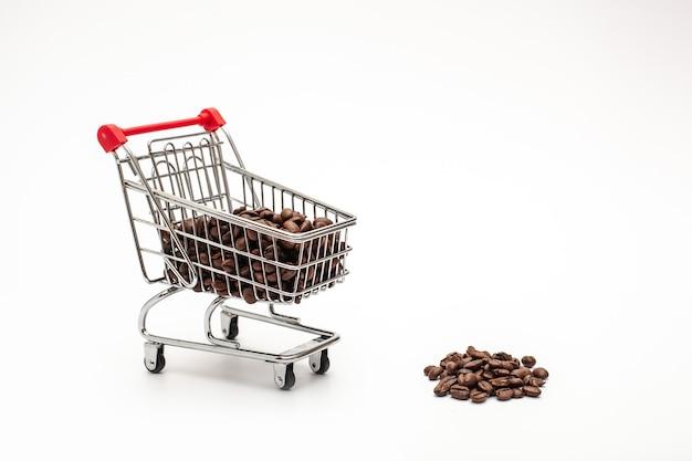 白い背景の上のコーヒー豆とショッピングカート。上面図、分離。コーヒー産業の概念。