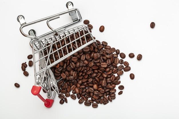 白い背景の上のコーヒー豆とショッピングカート。