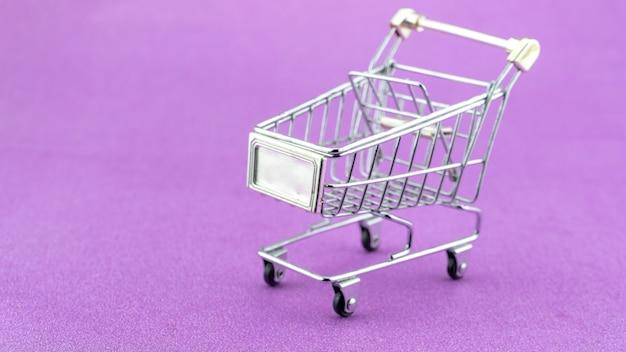 보라색 종이 배경에 동전이 있는 쇼핑 카트 쇼핑 컨셉 비즈니스를 위한 카트에 스톱 모션 태국 목욕 동전의 개념