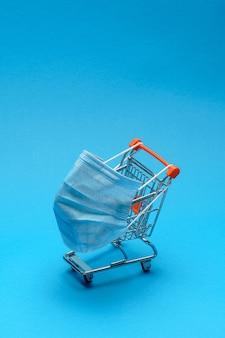 コピースペースで青い背景に分離されたコロナウイルス医療マスク付きのショッピングカート。