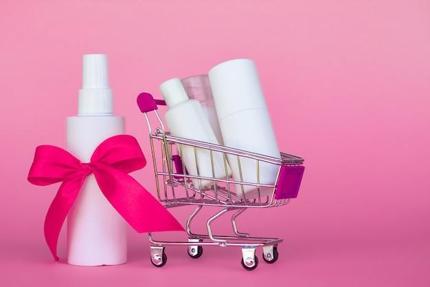 분홍색 배경에 밝은 분홍색 리본으로 화장품 병 쇼핑 카트. 공간을 복사하십시오.