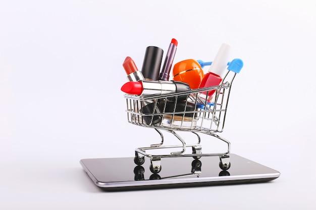 화장품 쇼핑 카트가 스마트 폰에 있습니다. 온라인 판매 개념.