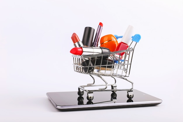 Shopping cart with cosmetics is on the smartphone. online sales concept.