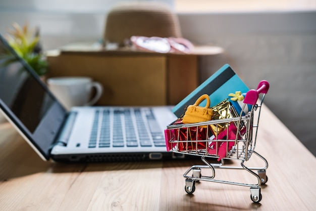 Shopping cart with credit card and woman accessories with laptop