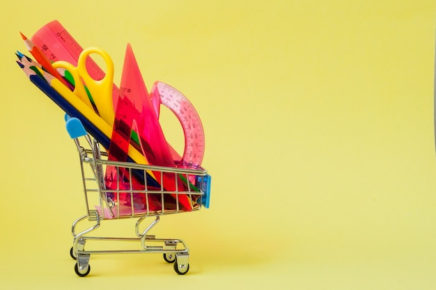 Shopping cart with different stationery on the yellow background.