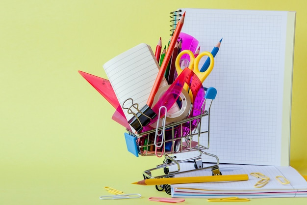 Shopping cart with different stationery on the yellow