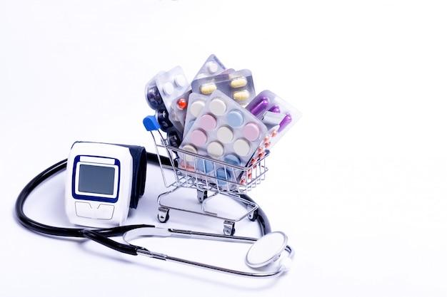 Корзина с различными таблетками и таблетками, стетоскоп и прибор для измерения давления