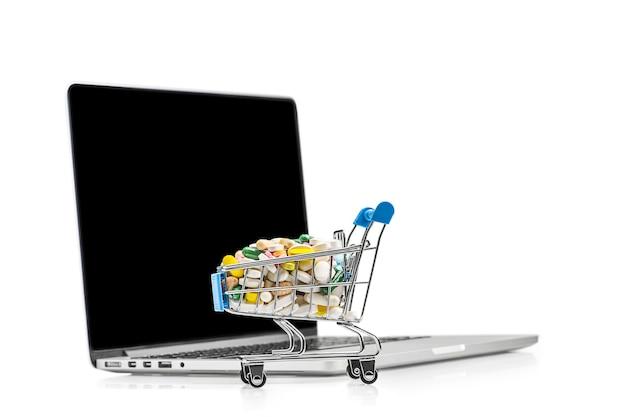Корзина с различными планшетами возле ноутбука. покупка лекарств и медикаментов в интернете.