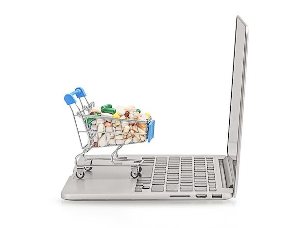 Корзина с различными планшетами на клавиатуре ноутбука. понятие медицины онлайн-покупок. интернет-аптеки.