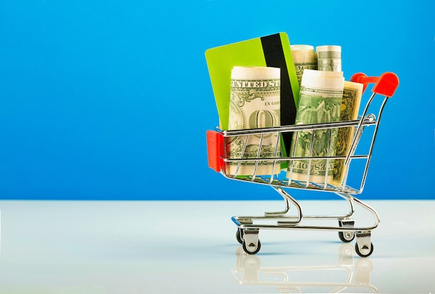 ドルとクレジットカードのショッピングカートのクローズアップショット。