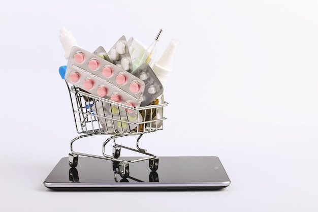 Shopping cart with drugs and pills is on the smartphone. online sales concept.