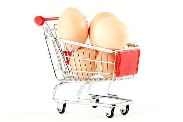 Shopping cart with eggs on the white background