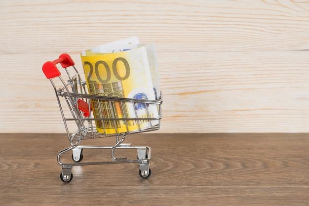 Корзина с банкнотами евро на деревянный стол