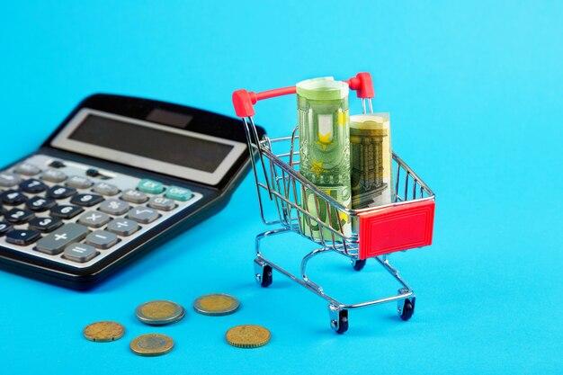 ユーロ、電卓付きのショッピングカート。金融の概念。