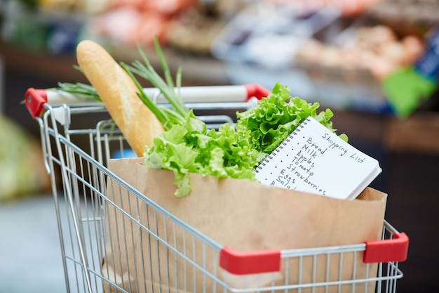 Shopping cart with fresh groceries, focus on shopping list in paper bag