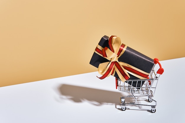 Shopping cart with gift box on beige gray background. gifts wrapped in kraft black paper with ribbon and bow. holiday shopping concept.