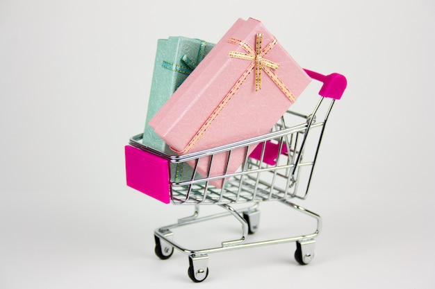 Shopping cart with gift boxes on light background