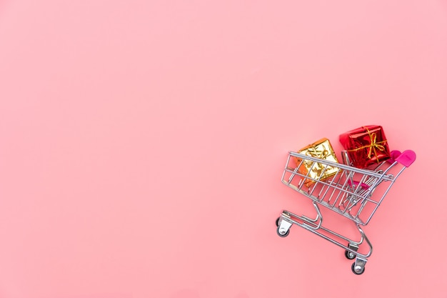 Shopping cart with gift boxes on pink background. shopping, shopping online concept, copy space, top view