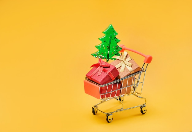 Shopping cart with gifts and a christmas tree on a yellow background with copy space.