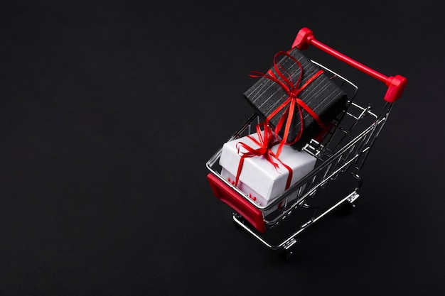 Shopping cart with gifts on dark background