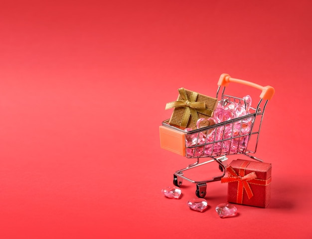 Shopping cart with gifts and glass hearts on a red background