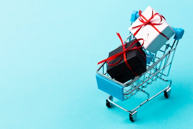 Shopping cart with gifts on plain background