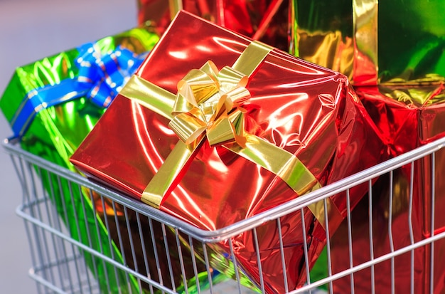 Shopping cart with gifts in supermarket background