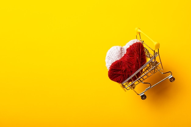 Shopping cart with handmade hearts flies on a bright yellow background.