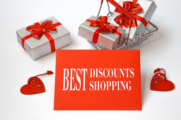 휴일 구매 및 텍스트 best discounts best shopping 레드 카드, 흰색 테이블에 쇼핑 카트.