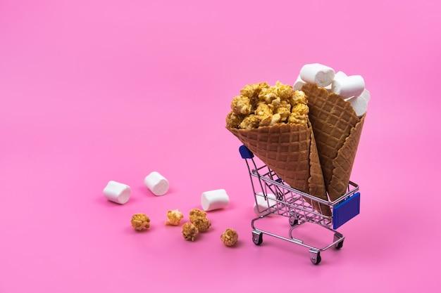 ピンクの背景にアイス クリーム コーンが入ったショッピング カート