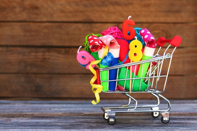 Shopping cart with items for birthday celebration on wooden background.