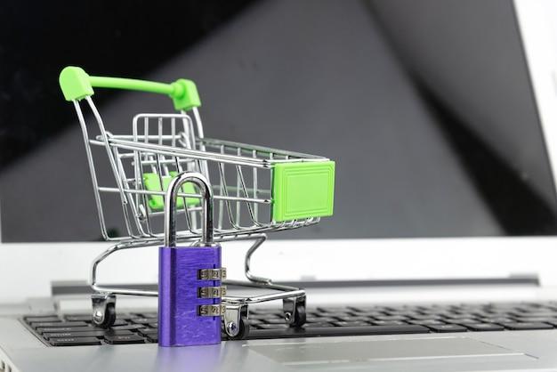 노트북 배경에 잠금 키와 쇼핑 카트입니다. 쇼핑, 투자, 구매 개념. 보안 및