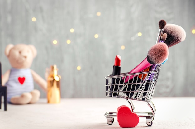 Shopping cart with make up brushes, red lipstick and heart shape. teddy bear and fairy lights background