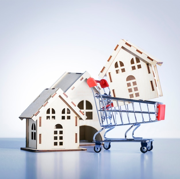 Shopping cart with model of house on gray background. buy property concept.