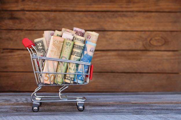 さまざまな国からのお金でショッピングカート:ドル、ユーロ、グリブナ、ルーブルの古い木材の背景。
