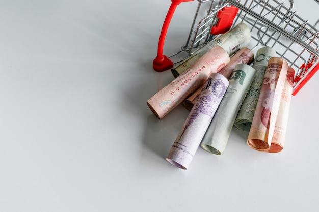 Shopping cart with the money (thai money) inside is upside down on white . top view