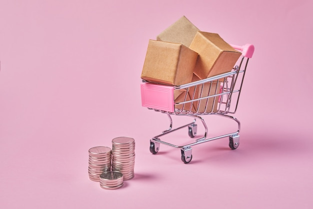 패키지 상자와 분홍색 배경에 동전 쇼핑 카트. 소포로 가득 찬 쇼핑 카트.