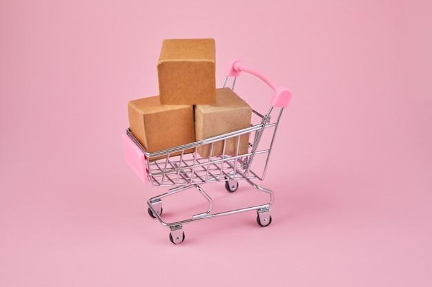 ピンクの背景にパッケージボックスが付いたショッピングカート。小包でいっぱいのトロリーを買う。