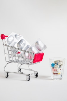 Shopping cart with pill blister and medicines in glass on white background