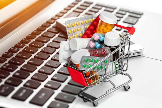 Shopping cart with pills isolated on background