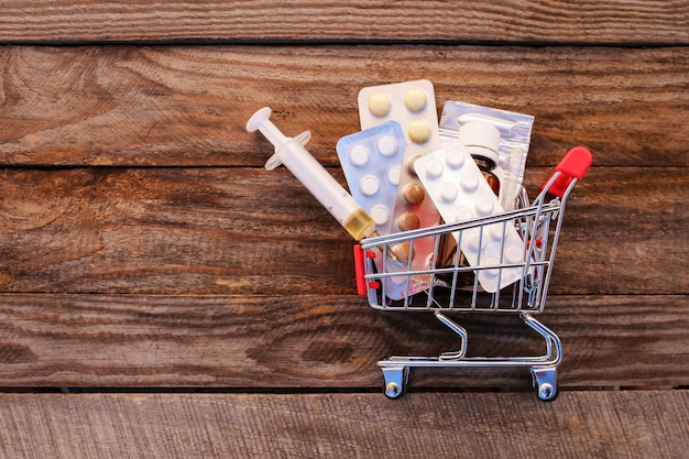 Shopping cart with pills, syringe on the old wood background