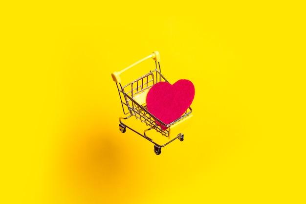 핑크 하트와 쇼핑 카트는 밝은 노란색 배경에 날아간 다.