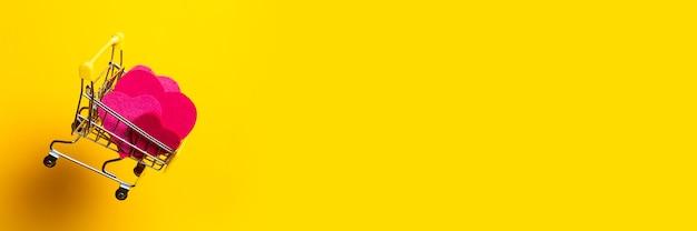 핑크 하트와 쇼핑 카트는 밝은 노란색 배경에 날아간 다. 배너.